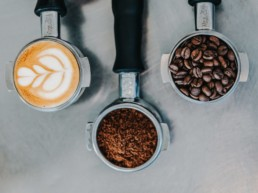 A photo of three portafilters filled with coffee, ground coffee and coffee beans